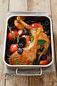 Roast duck leg with dried plums and apples
