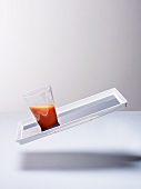 A glass of carrot juice on a tilted tray