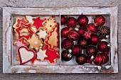Weihnachtskekse und Christbaumkugeln im Holzrahmen