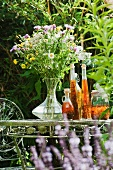 Meadow flowers and herbal essence on a garden table