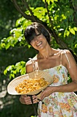 A woman holding a straw hat full of chanterelle mushrooms in a garden
