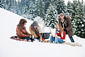 Friends drinking tea by a fire in the snow