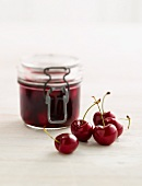A jar of cherry jam and fresh cherries