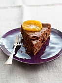 A slice of brownie cake topped with an orange slice