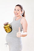 A pregnant woman holding a jar of gherkins