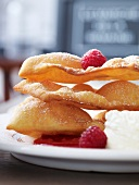 French carnival pastries with raspberries, raspberry sauce and cream