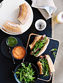 Grilled sausages with a duo of sauces and rocket on bread