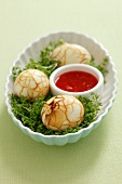 Eggs boiled in tea on a bed of cress with chilli sauce (China)