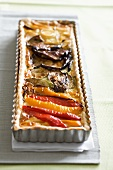 Quiche with antipasti vegetables in a baking tin