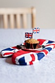 Ein Muffin mit englischem Fähnchen auf Backhandschuh
