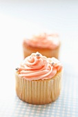 Cupcakes topped with pink frosting and silver balls