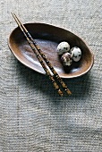 Three Quail Eggs in a Dish with Chopsticks