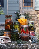 Preserved fruit and vegetables in jars on a wall outside