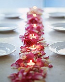 Roses, rose petals and tea lights as table decoration