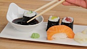 Picking up maki sushi with chopsticks and dipping in soy sauce