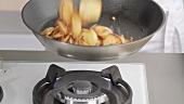 Tossing sauté potatoes with lardons in a frying pan