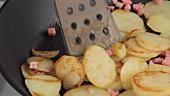 Bratkartoffeln mit Speckwürfeln in einer Pfanne
