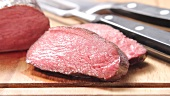 Sliced, rare roasted venison saddle fillet