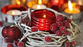 A tealight in a red glass holder and Christmas decorations