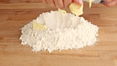Chopped butter being placed on a pile of flour