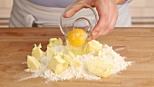 An egg being added to a pile of flour and butter
