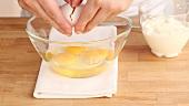 Eier in eine Schüssel aufschlagen