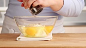 Egg topping being made: creme fraiche and eggs being seasoned and stirred