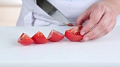 A tomato being cut into eighths