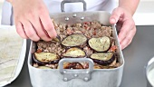 Moussaka being made: aubergine slices and minced meat being layered in a baking dish