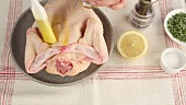 A whole chicken being brushed with melted butter