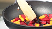 Beetroot and carrots being fried in a pan