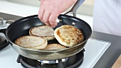 English muffins being toasted in a pan