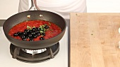 Tomato sauce being seasoned with fresh herbs and olives