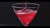 Cosmopolitan in ein Cocktailglas gießen