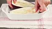 Ausgehöhlte Auberginenhälften in eine geölte Auflaufform legen