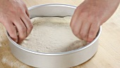 Pizza dough being rolled out and place in a deep pizza dish