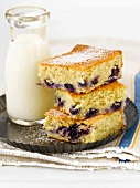 Squares of Blueberry Buckle Cake Stacked with a Bottle of Milk