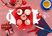 Cupcakes mit englischen Fähnchen in einer Box und eine Tasse Tee