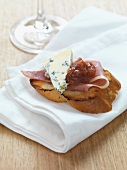 A slice of toasted baguette topped with raw ham, blue cheese and rhubarb chutney