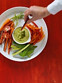 A hand dipping a carrot into garlic and basil aioli