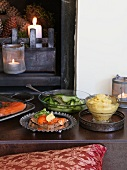 Salmon, bread and lettuce in front of a fireplace