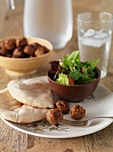 Pork meatballs with unleavened bread and a mixed leaf salad