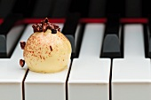 A white chocolate praline on a piano