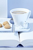 An espresso cup and amarettini with doll's crockery