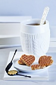 A cup of tea, heart-shaped waffles and a mini waffle iron