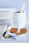 A cup of tea, heart-shaped waffles and a mini waffle iron