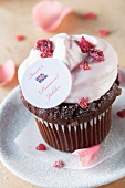 A chocolate cupcake topped with cream, candied rose petals and a Union Jack decoration