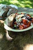 Greek Salad with Feta Cheese, Tomatoes, Olives and Red Onion; With Bread; On Outdoor Table