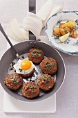 Meat balls with a fried egg, caper butter and sardines