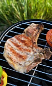 A grilled pork chop on a barbecue